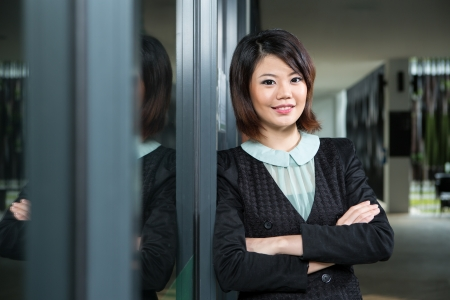 business: Asian Business woman leaning against a window.