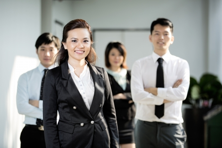 Chinese Business woman standing with her colleagues in the background. Stock Photo - 16771725
