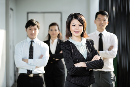 staff meeting: Chinese Business woman standing with her colleagues in the background.