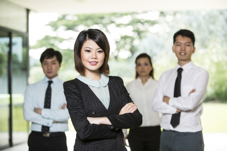 confident consultant: Chinese Business woman standing with her colleagues in the background.