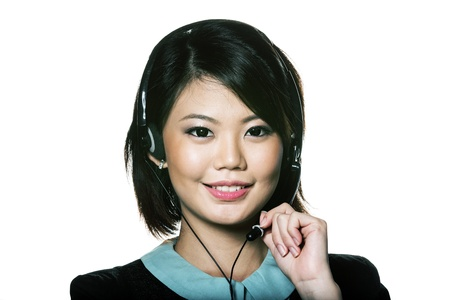 Portrait of a friendly Chinese receptionist wearing headset. Isolated on white. photo