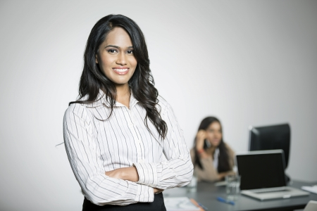 Indian Business woman with her colleague in the background working. photo