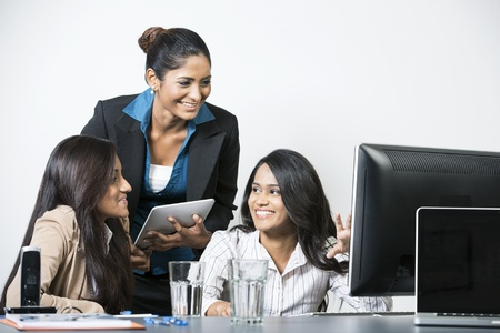 Happy Indian business women working on an assignment. photo