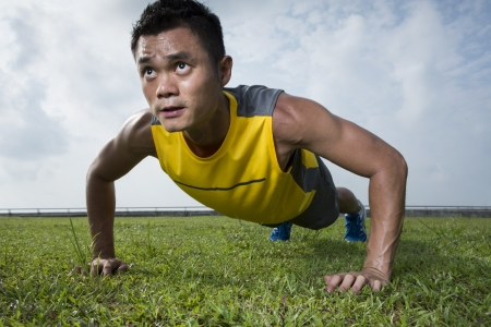 pushup: Chinese man performing push up in the city park Stock Photo
