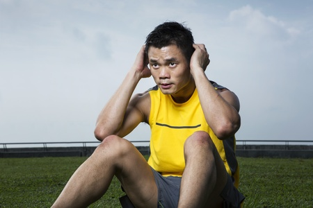 Chinese man performing abdominal crunch exercie in the park Stock Photo - 17719127