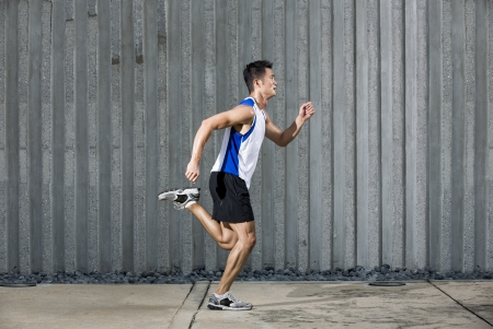 man side view: Athlete Chinese man running in urban city. Asian Runner jogging outdoors with a wall in background. Male fitness concept. Stock Photo