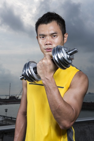 Muscular Asian man exercising with weight training equipment at a sports gym. Stock Photo - 17719093