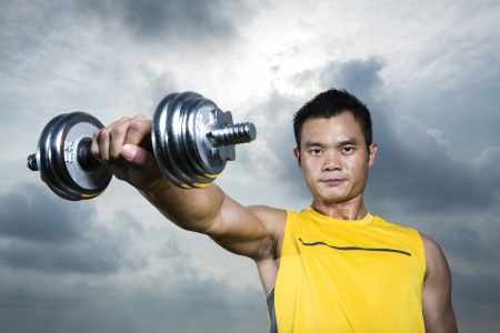 moody: Muscular Asian man exercising with weight training equipment at a sports gym.