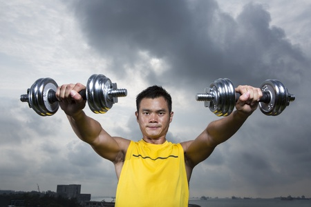 Muscular Asian man exercising with weight training equipment at a sports gym. Stock Photo - 17719109