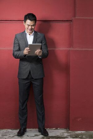 Full length portrait of a Chinese man with a tablet computer. Asian business man reading a digital tablet computer, leaning against a red wall. photo