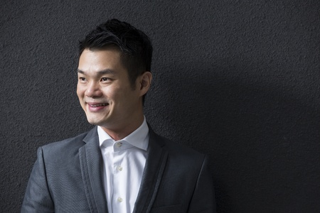 man front view: Chinese Business man leaning on a black wall. Handsome young Chinese business man leaning against a black wall and looking away. Stock Photo