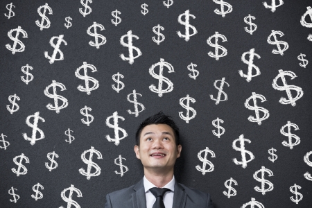 Chinese businessman in front of lots of dollar signs written on a blackwall. Concept about money and success. Stock Photo - 18191930