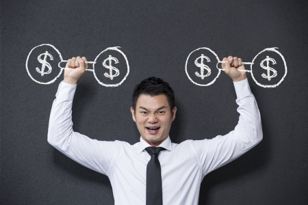 Chinese man lifting dumb bell weights with dollar sign on them. Concept about success and money. photo