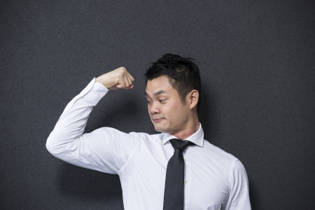 Chinese business man flexing his large bicep. Concept about power and strength. photo