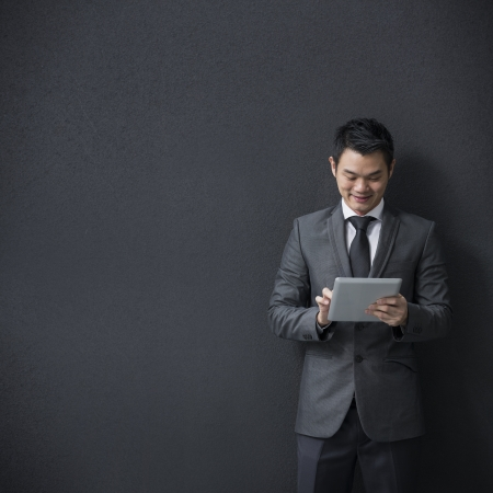 asian business man: Chinese man with a tablet computer. Asian business man using digital tablet computer, leaning against a black wall.