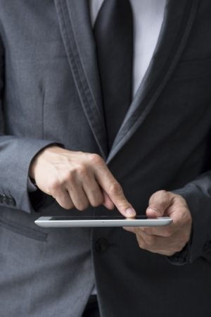 Closeup of a Chinese man with a tablet computer. Asian business man using digital tablet computer, leaning against a black wall. Stock Photo - 18172581