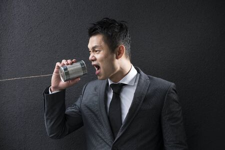 tin can: Conceptual image is about communication. Chinese Business man shouting into a Tin Can Phone. Asian Business man  with Tin Can Phone. Concept about communication.