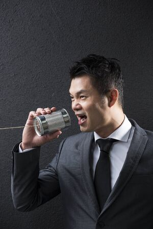 south asian ethnicity: Conceptual image is about communication. Chinese Business man shouting into a Tin Can Phone. Asian Business man  with Tin Can Phone. Concept about communication.