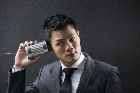 Conceptual image is about communication. Chinese Business man Listening to a Tin Can Phone. Asian Business man with Tin Can Phone. Concept about communication.  photo