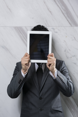 guise: Businessman holding a digital tablet up over his face. Business man covering face with touchpad pc.