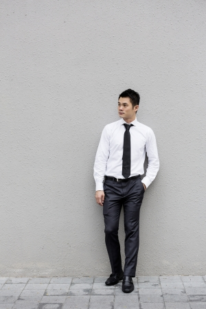 Chinese Business man leaning on a black wall. Handsome young Chinese business man leaning against a grey wall. photo