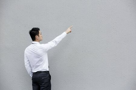 Rear view of a Chinese Business man pointing his finger at a grey wall.  photo