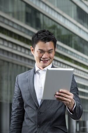 Chinese man with a tablet computer. Asian business man using digital tablet computer with a blurred office buildings as a background. photo