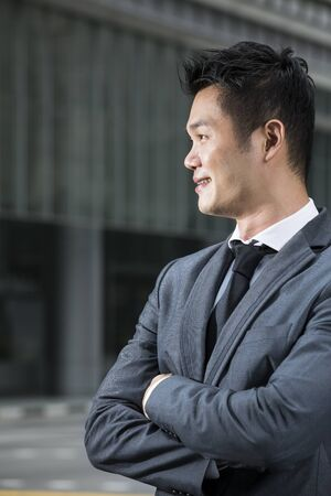 Closeup of a happy young Chinese business man looking away. Asian man smiling & looking away with blurred office buildings as a background. Stock Photo - 18191946