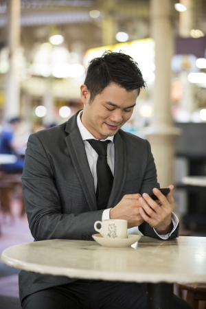 the stalls: Chinese business man drinking a cup of coffee while sitting with his phone in an Asian food court or Hawker centre cafe.