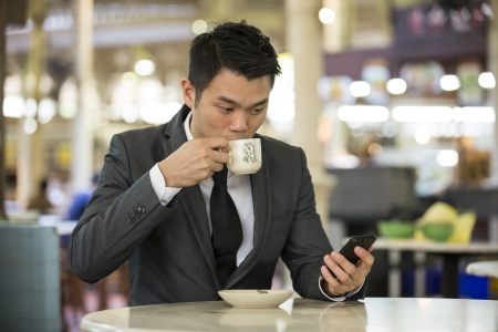 street vendor: Chinese business man drinking a cup of coffee while sitting with his phone in an Asian food court or Hawker centre cafe.