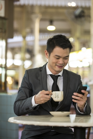 Chinese business man drinking a cup of coffee while sitting with his phone in an Asian food court or Hawker centre cafe.