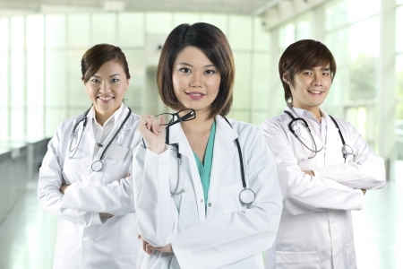 Team of Chinese doctor's wearing a white coat and stethoscope. Three Asian doctors wearing lab white coats standing in a hospital. photo
