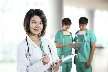 Portrait of a cute Female Chinese doctor wearing a green scrubs and a lab coat holding a clipboard. Two Portrait male Chinese medics standing in background. photo