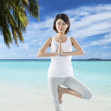 Portrait of a beautiful Chinese woman doing yoga exercise on a perfect tropical beach. photo