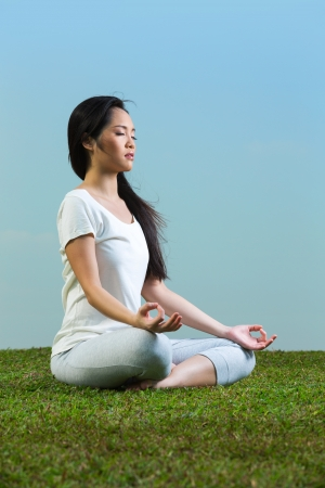 Portrait of young beautiful Chinese woman sitting meditating and in a yoga pose on grass photo