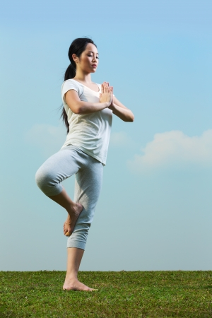 Portrait of young beautiful Chinese woman meditating and in a yoga pose on grass photo