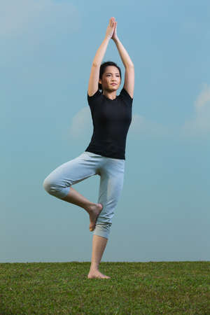 Young beautiful Chinese woman standing meditating in a yoga pose on grass. Asian Woman in black t-shirt Performing yoga. photo