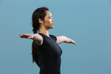 Close up portrait of a beautiful Chinese woman standing meditating in a yoga pose. Asian Woman in black t-shirt Performing yoga. photo