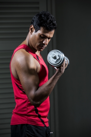 Muscular Asian man exercising with weight training equipment at a sports gym.  photo