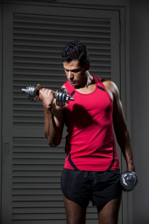 Muscular Asian man exercising with weight training equipment at a sports gym.  Stock Photo