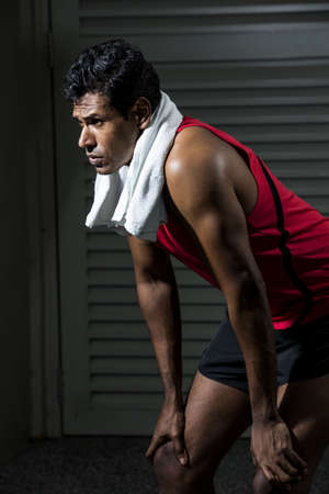 Portrait of an Indian man resting after exercise in the gym. photo