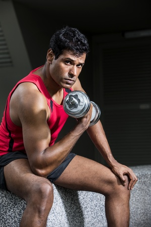 Muscular Asian man exercising with weight training equipment at a sports gym.