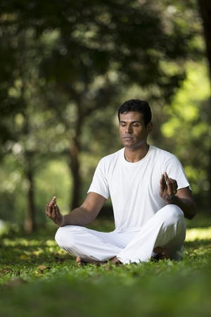 Portrait of handsome Indian man doing yoga exercise in park photo