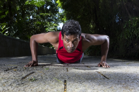 Indian man performing push up in the city park. Male fitness concept. photo