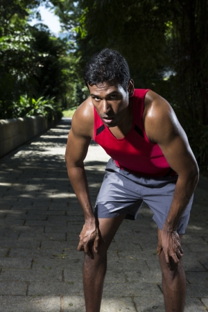 Athletic Indian man having a break from running. Asian Runner jogging in the park. Male fitness concept. photo