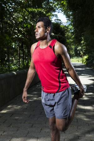 Sporty Young Indian man stretching outdoors in city park photo