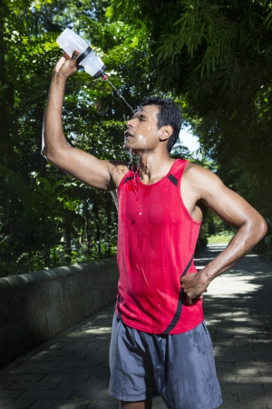 cool down: Indian man pouring water on himself to cool down after finishing a run. Male fitness concept.
