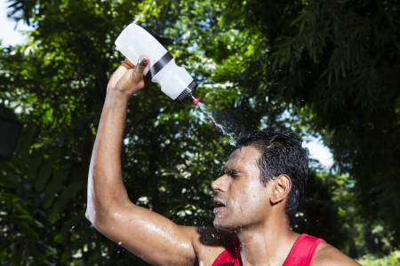 tiredness: Indian man pouring water on himself to cool down after finishing a run. Male fitness concept.