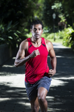 Athletic Indian man running in park. Asian Runner jogging outdoors with tree's in background. Male fitness concept. photo