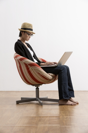 Portrait of a happy Chinese woman sitting on a chair using laptop  photo